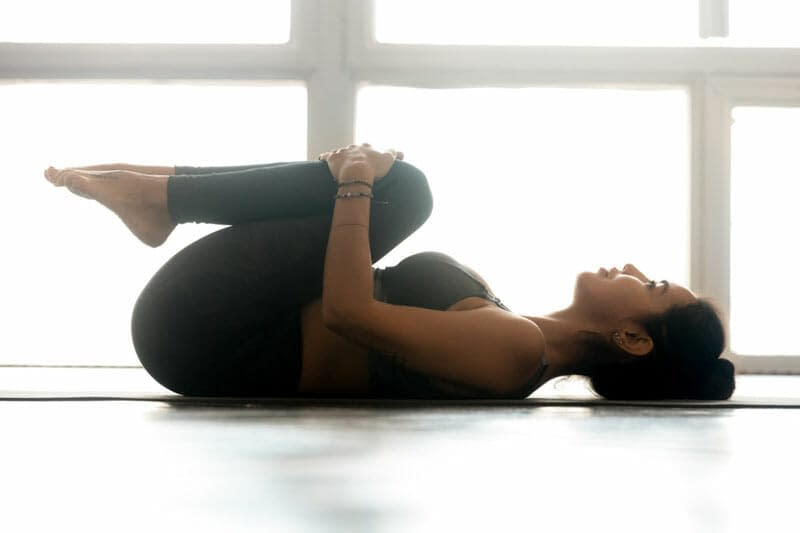 Knees-to-Chest Pose (Apanasana)- 9 Yoga Poses that Relieve Menstrual Cramps (With Variations)