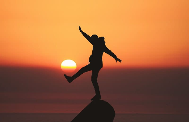 Person balancing against a sunset backdrop - Holistic Wellness Explained